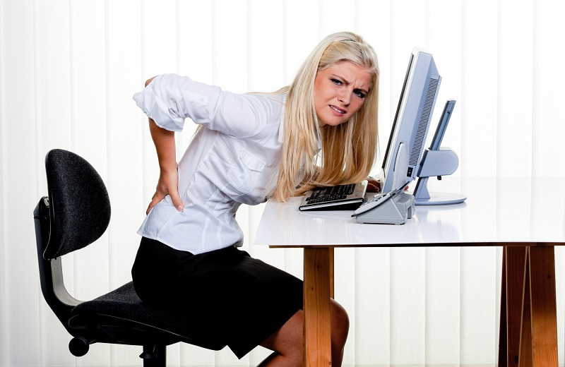 Young woman with pain in the back office.
