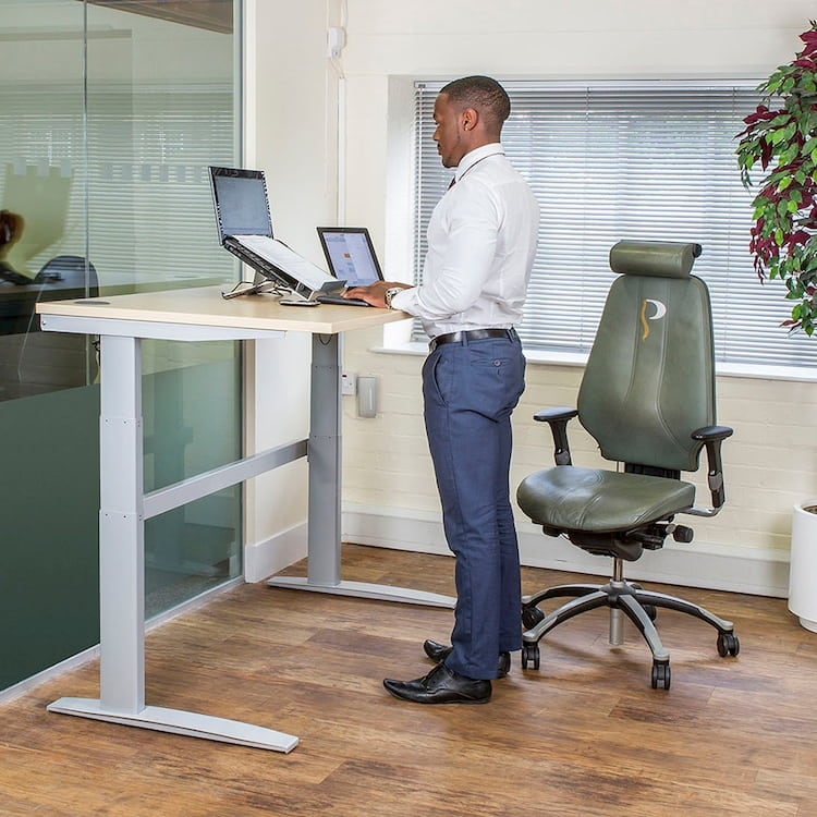 man at office with sit stand desk