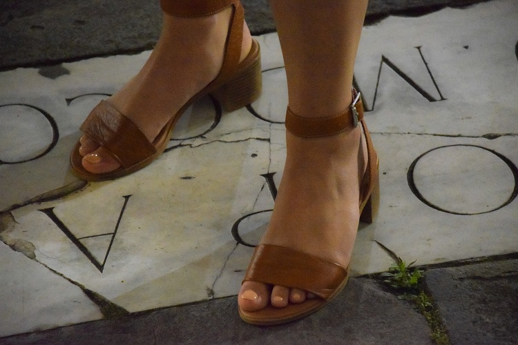 picture of a woman feet in a brown sandals standing on a marble and concrete