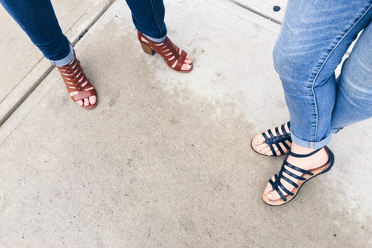 picture of girls legs standing on a concrete, wearing jeans and lace-up flats and heal