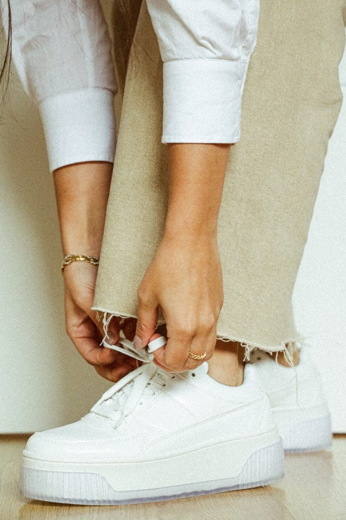 picture of a woman in pants and a white shirt tie a lace of white sneakers