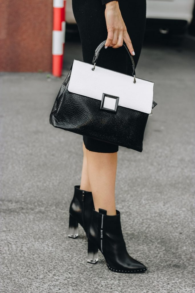 picture of a woman standing on a street wearing black dress, black and white bag and black ankle boots