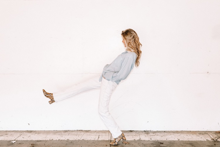 woman walking on a sidewalk in a comfortable shoes from snake skin, white pants and blue shirt