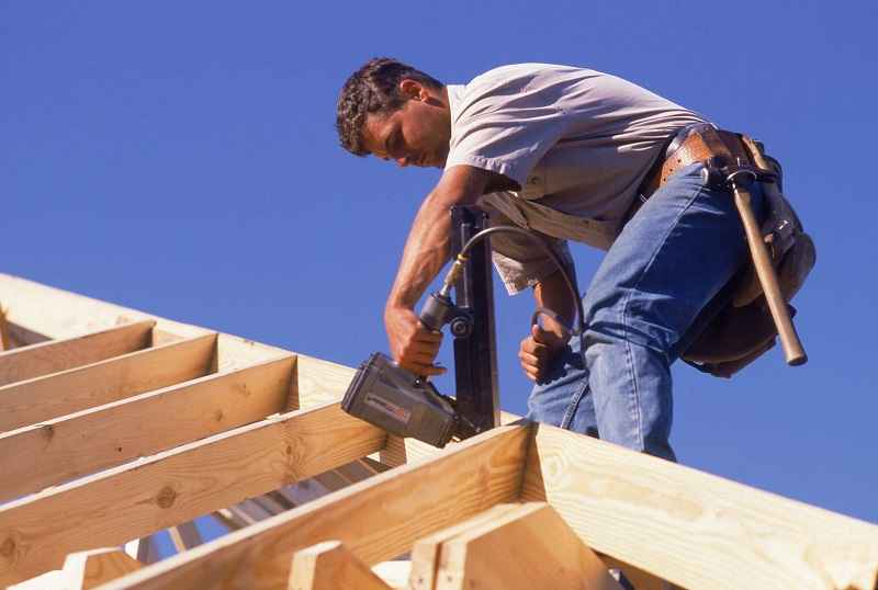 Worker working on a roof with roof nailer