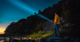 picture of a man holding flashlight beside a river in the mountains