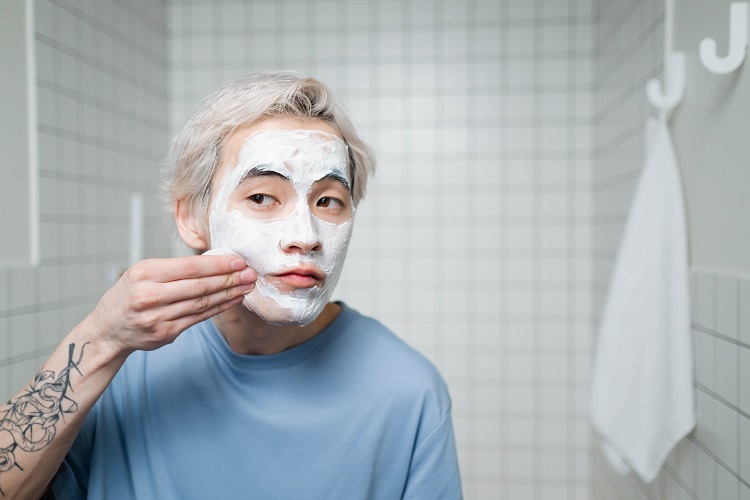 picture of a man applying a skincare product on his face